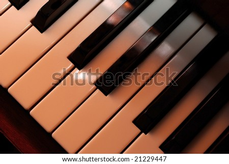 Piano keys close up using warm photo filter. Playing with light. - stock photo