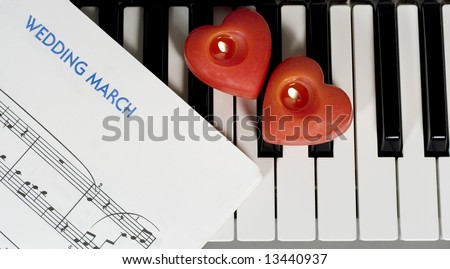 Piano keys with two heart-shaped candles and sheet music (Wedding March) - stock photo