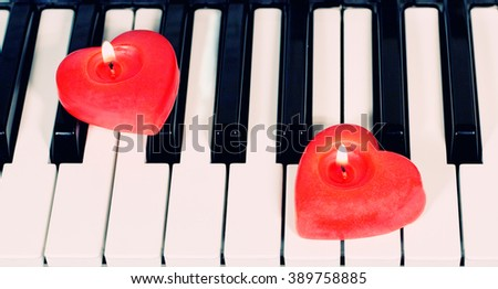 Piano keys with two heart-shaped candles (retro style) - stock photo