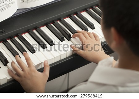 piano lesson, Asian boy kid activity playing piano with notes - stock photo