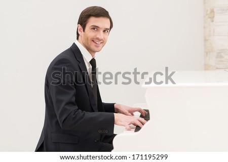 Piano man. Cheerful young man in formalwear playing piano and looking at camera - stock photo