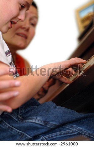 Piano teacher and student during a lesson.  The student's hands are the point of focus - stock photo