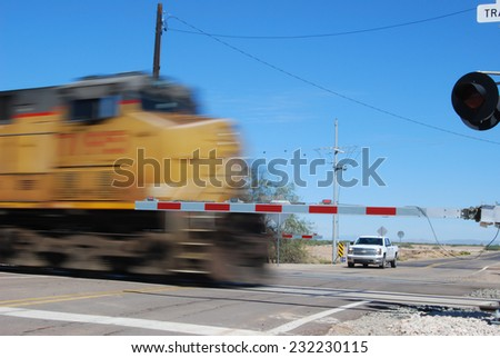 Picacho, AZ, USA - October 18, 2014: A speed blur of a locomotive passing through a railroad crossing with the gates down. Taken October 18, 2014