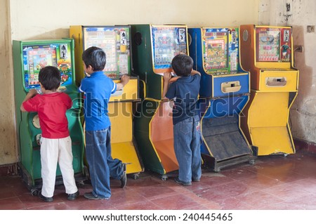 PICHUCALCO, CHIAPAS, MEXICO - DECEMBER 21, 2014: Three young boys entertain themselves by playing old Mexican bingo arcade games at the bus terminal in Pichucalco - stock photo