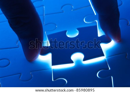 Pick puzzle piece with mystery back light - stock photo