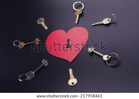 pick up the key from the heart of a black background - stock photo