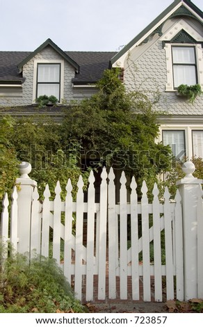 Picket fence entry gate leads to an overgrown front yard of an old house. - stock photo
