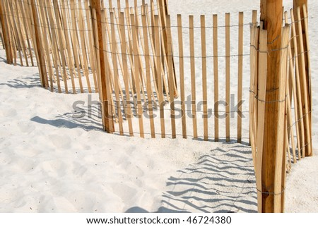 Picket fence on white sand beach in Panama City Florida USA. Used to protect and conserve the dune grass on the beach. - stock photo