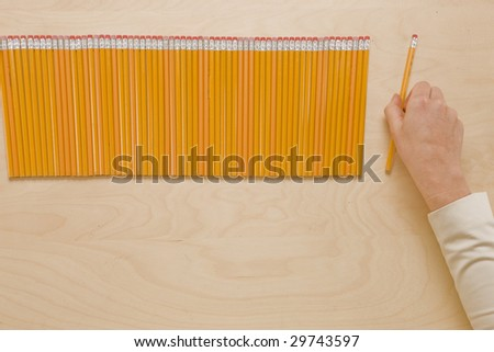 Picking Pencils - Hand picking pencil from perfect row - stock photo