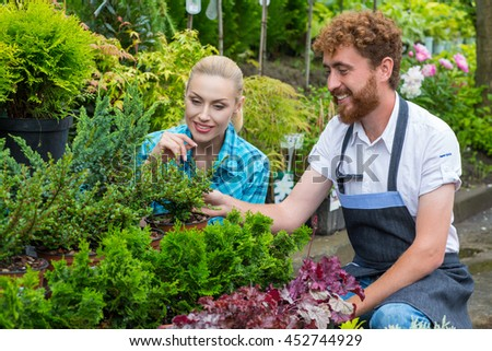 Picking the perfect plant. Beautiful blonde woman smiling cheerfully while the male florist helping her to pick a plant to buy at the local greenhouse