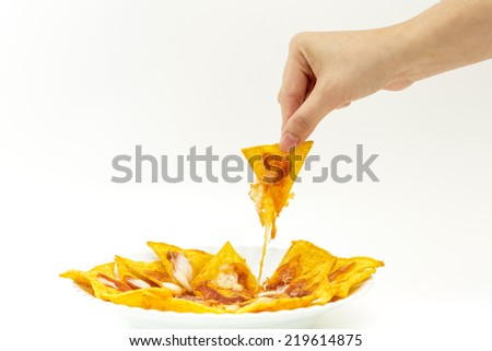 Picking tortilla chips covered with cheese (Nachos) from white dish on isolated white background - stock photo