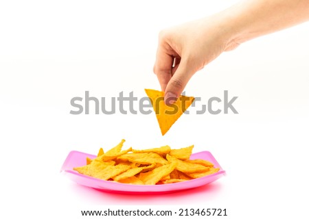 Picking tortilla chips from colorful dish  on isolated white background - stock photo