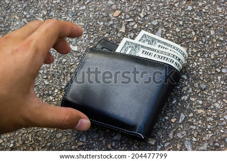 picking up a lost wallet - stock photo