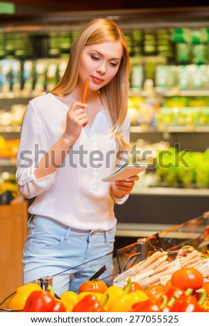 Picking up the products from her list. Thoughtful young women holding note pad and pen while standing in a food store - stock photo