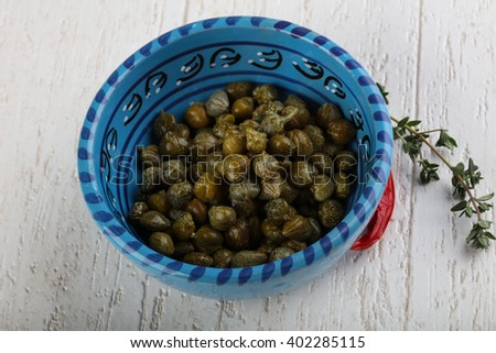 Pickled capers in the bowl on wood background - stock photo