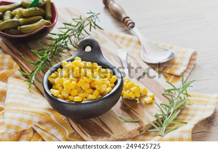 pickled corn and cucumbers in a bowl on a cutting board and rosemary on a wooden background. home preservation. selective focus - stock photo