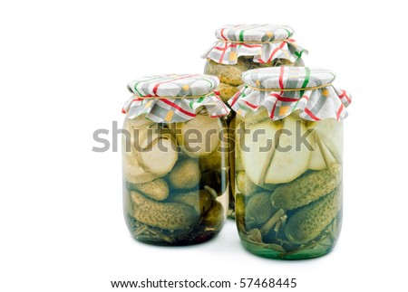 Pickled cucumbers and vegetable marrows in glass cans on the white background - stock photo