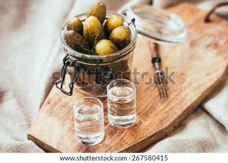 Pickled cucumbers in a small jar and two vodka  shots - stock photo