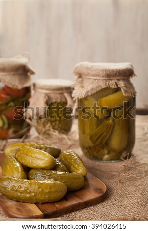 Pickled cucumbers in glass jars traditional salted homemade marinated vegetables on vintage table background - stock photo