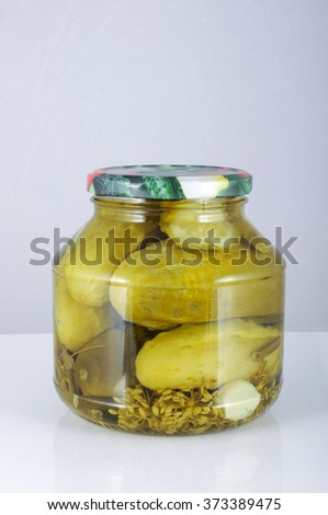 Pickled cucumbers in the jar isolated on the grey background