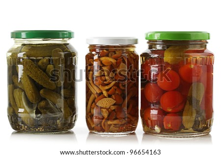 Pickled cucumbers, tomatoes and mushrooms on a white background.