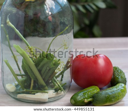 Pickled cucumbers with herbs and spices in glass jar. Pickles gherkins salted cucumbers still life on old planks. Pickled tomatoes.  - stock photo