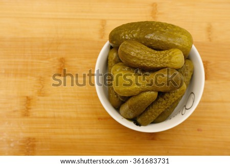 Pickled gherkins in a small white plate on a wooden background - stock photo
