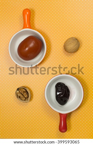 Pickled plum in the red plate. Pickled tomatoes in orange plate. Two walnuts on yellow. Top view - stock photo