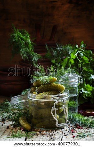 Pickled small cucumbers gherkins in a glass jar with dill, herbs and spices on an old wooden table, selective focus - stock photo