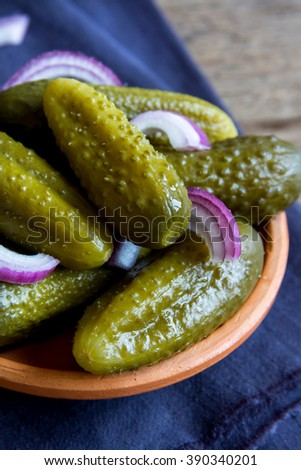 Pickles in ceramic bowl over rustic wooden background close up