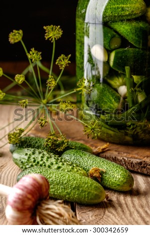 Pickles on wooden table. Homemade cucumber preserved in glass jar. - stock photo