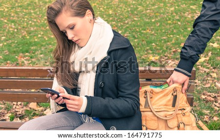 Pickpocketing from the bag of a young woman in a park - stock photo
