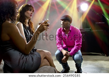pickup artists harrassing women at a nightclub - stock photo