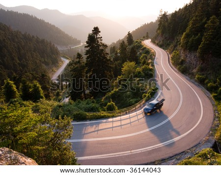 pickup crosses mountain road winding in twilight - stock photo