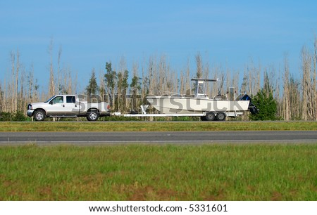 Pickup truck towing boat on trailer - stock photo