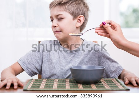 Picky eater boy refusing to eat disgusting food - stock photo