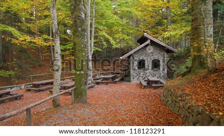 picnic area with small stone house  in autumn forest - stock photo