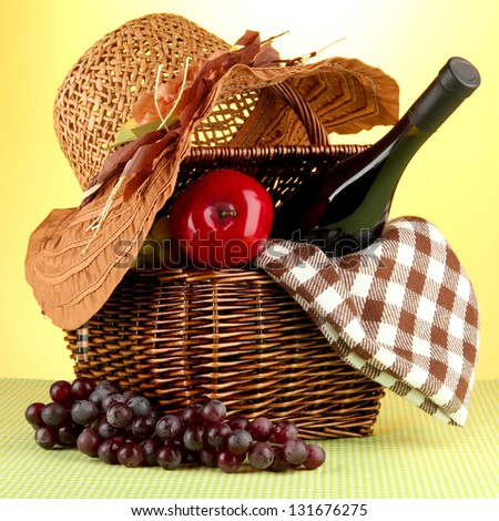 Picnic basket and bottle of wine on cloth on yellow background