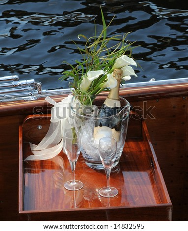 Picnic basket and champagne - on a boat - stock photo