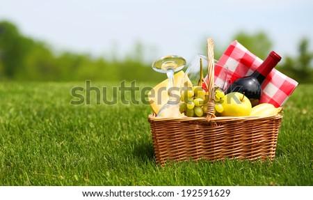 Picnic basket on green field - stock photo
