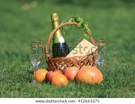 Picnic basket on green grass in park - stock photo