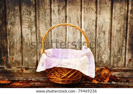 Picnic basket with autumn leaves against an old wooden wall. - stock photo