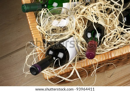 Picnic basket with bottles of red and white wine and wineglass in straw. - stock photo