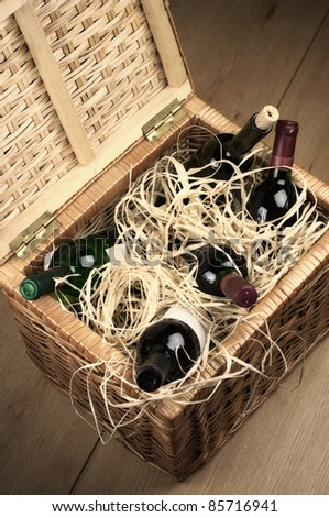 Picnic basket with bottles of red and white wine in straw. - stock photo