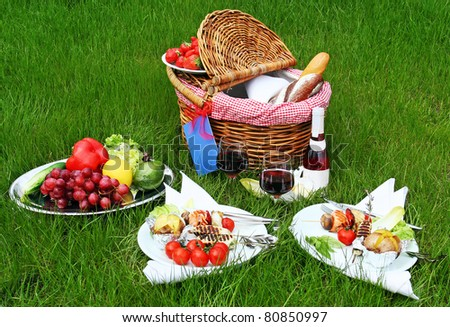 Picnic basket with different food on grass - stock photo