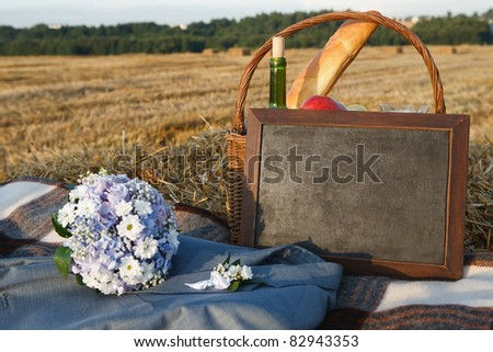 picnic basket with diffferent sorts of snacks; Black board empty blank sign horizontal and bridal bouquet on a blanket - stock photo