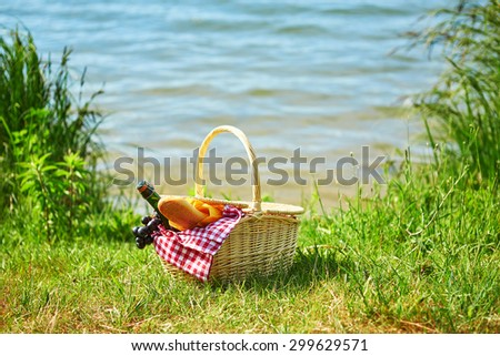 Picnic basket with food and cider bottle near the water