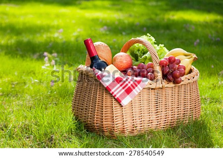 Picnic basket with food on green sunny lawn. - stock photo