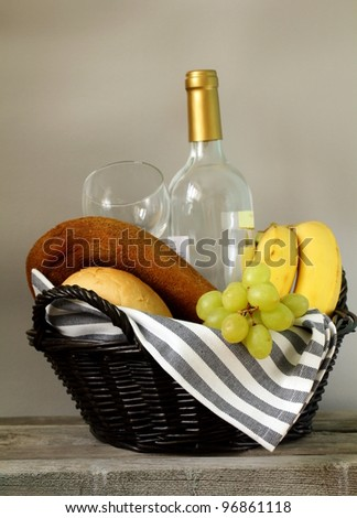 Picnic basket with fresh fruit , bread and wine