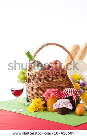Picnic basket with fruits and wine isolated on white  - stock photo